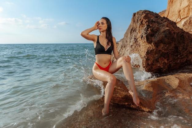 Seksowna dziewczyna w czerwonym stroju kąpielowym siedzi na plaży
