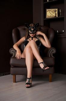Seksowna dziewczyna w masce i skórzanym pasku siedzi na krześle