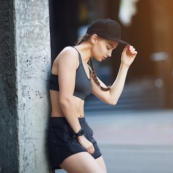 Seksowna dziewczyna w odzieży sportowej na tle szarych drzwi garażowych