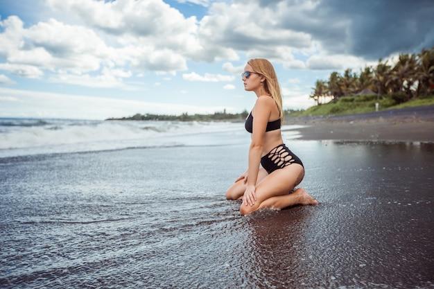 Seksowna dziewczyna w stroju kąpielowym siedzi na plaży z czarnym piaskiem
