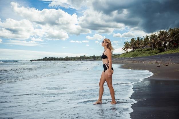 Seksowna dziewczyna w stroju kąpielowym spaceruje po czarnej plaży
