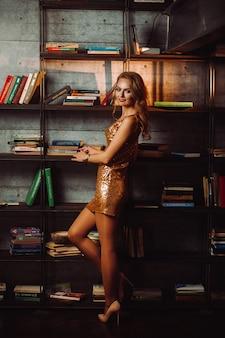 Seksowna dziewczyna w złotej sukience na tle książek w bibliotece. model z długimi włosami i czerwoną szminką we wnętrzu.