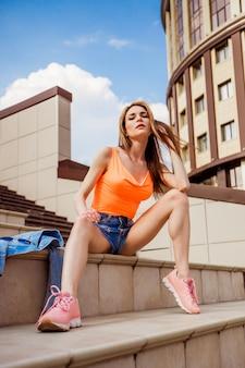 Seksowna dziewczyna z długimi nogami w krótkich spodenkach w mieście