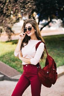 Seksowna dziewczyna z długimi włosami w okularach przeciwsłonecznych pozuje na ulicy. ma marsala na ubraniach i wygląda na zadowoloną.