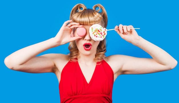 Seksowna dziewczyna z lizakiem i makaronikami. młoda kobieta zakrywa oczy kolorowym cukierkiem i makaronikiem.