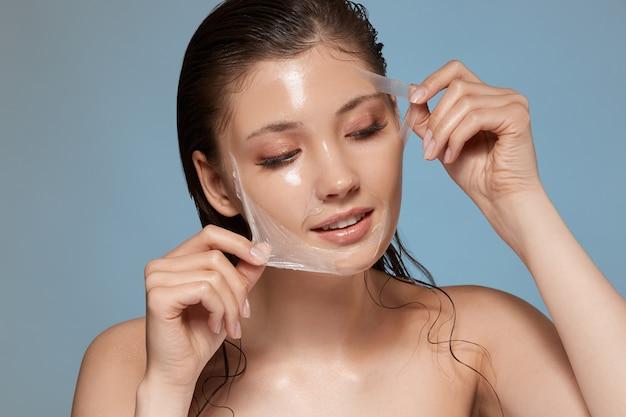 Seksowna dziewczyna zdejmuje przezroczystą maseczkę na twarz i patrzy w bok