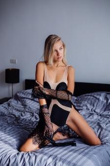 Seksowna europejska kobieta w sypialni o wschodzie słońca w beżowym body i czarnej przezroczystej koronkowej pelerynie