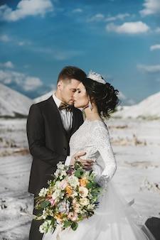 Seksowna i piękna brunetka modelka ze stylową fryzurą i diademem, w białej koronkowej sukni i stylowych przystojnych mężczyznach w modnym garniturze pozujących razem na pustyni w soli