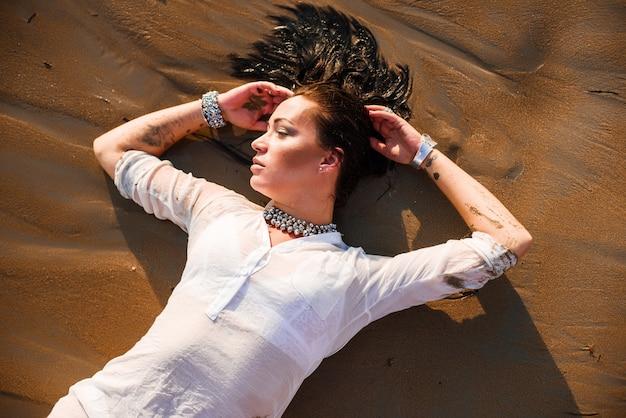 Seksowna i piękna kobieta kłama w mokrym piasku na plaży