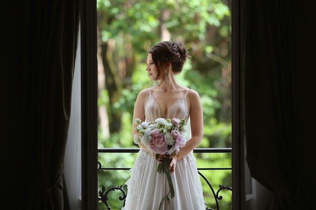 Seksowna i piękna modelka w stylowej i modnej koronkowej sukni ślubnej z nagimi ramionami pozuje w luksusowym wnętrzu vintage