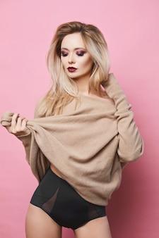 Seksowna i zmysłowa modelka blondynka o niebieskich oczach, idealnym ciele i jasnym makijażu, w czarnej stylowej bieliźnie i fascynującej bluzie pozuje na różowym tle