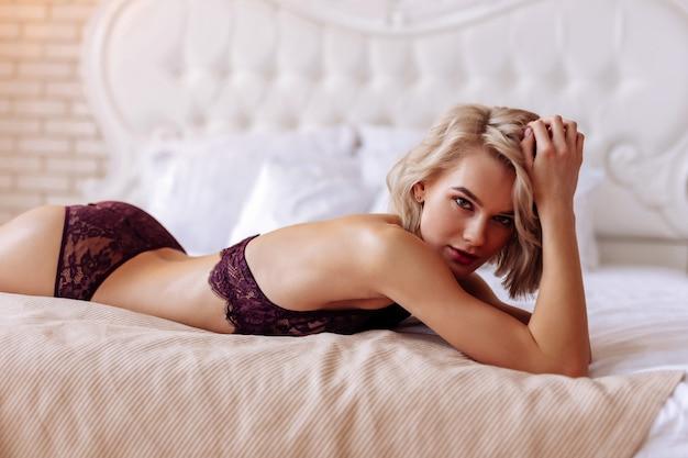 Seksowna jasnowłosa obiecująca modelka pozuje promując markę bielizny