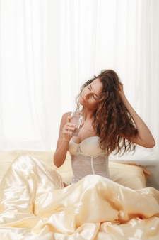 Seksowna kędzierzawa szczupła caucasian dziewczyna siedzi w rannym łóżku trzyma szklankę wody