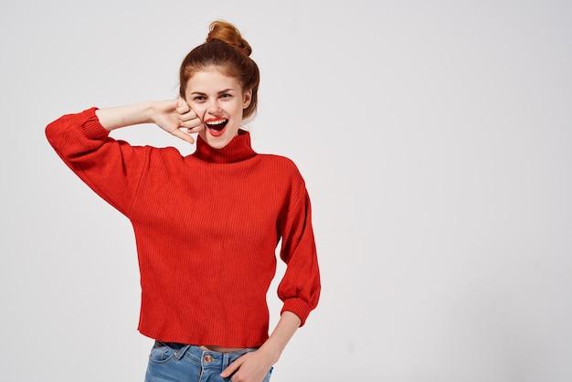 Seksowna kobieta gestykuluje rękami w czerwonym swetrze