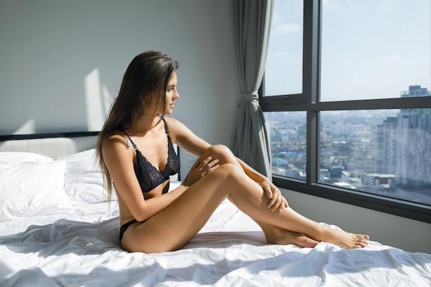 Seksowna kobieta jest ubranym czarnego bielizny obsiadanie na łóżku