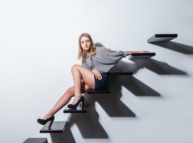 Seksowna kobieta leżąca na schodach nad szarym bakground