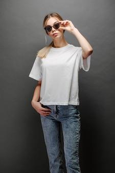 Seksowna kobieta lub dziewczyna ubrana w białą pustą koszulkę z miejscem na logo, makietę lub projekt w swobodnym miejskim stylu