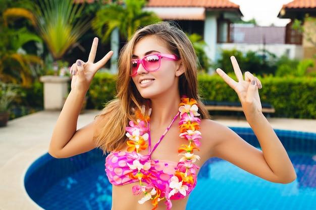 Seksowna kobieta na wakacjach, zabawy na basenie, ubrana w bikini i różowe okulary przeciwsłoneczne, tropikalne kwiaty, kolorowy letni styl mody