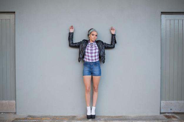 Seksowna kobieta pozuje na popielatej ścianie