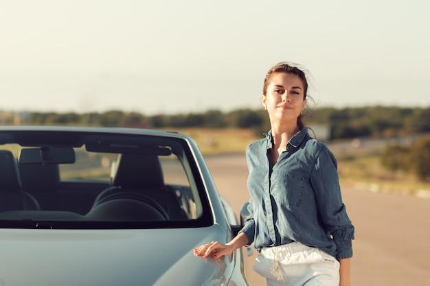 Seksowna kobieta pozuje obok cabrio samochodu
