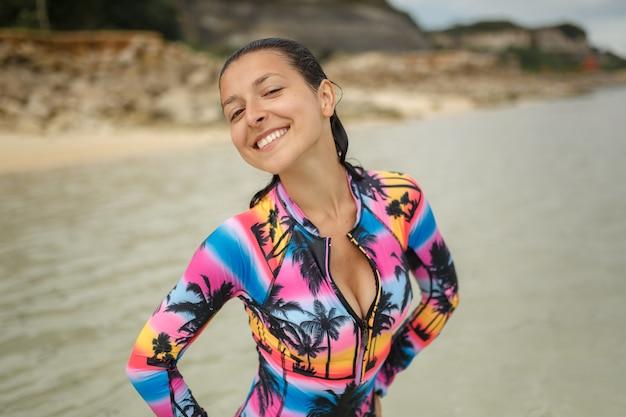 Seksowna kobieta pozuje przy ocean plażą.