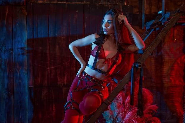 Seksowna kobieta pozuje w czerwonym kostiumie bdsm, wnętrze opuszczonej fabryki. młoda dziewczyna w erotycznej bieliźnie, fetysz seksu, fantazje seksualne