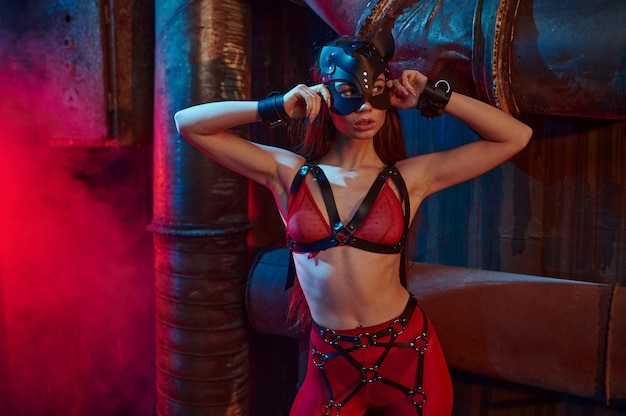 Seksowna kobieta pozuje w garniturze bdsm i skórzanej masce, wnętrze opuszczonej fabryki. młoda dziewczyna w erotycznej bieliźnie, fetysz seksu, fantazje seksualne