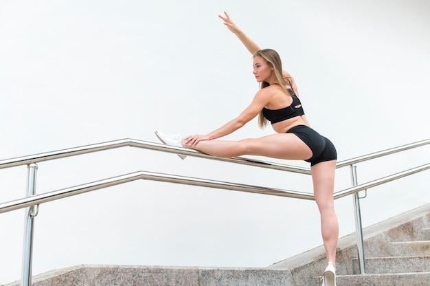 Seksowna kobieta robi sprawności fizycznej ćwiczy długi strzał