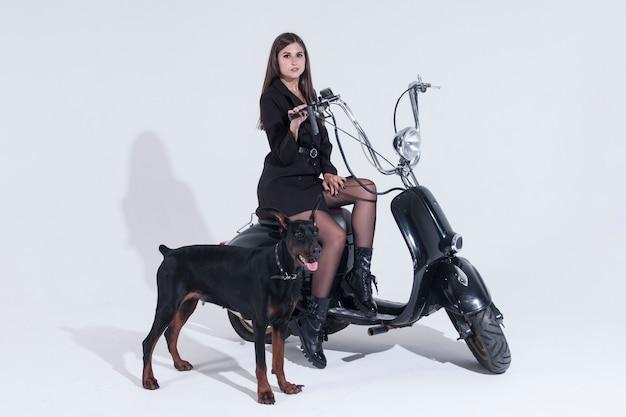 Seksowna kobieta siedzi na motocyklu. czarny doberman strzeże kochanki