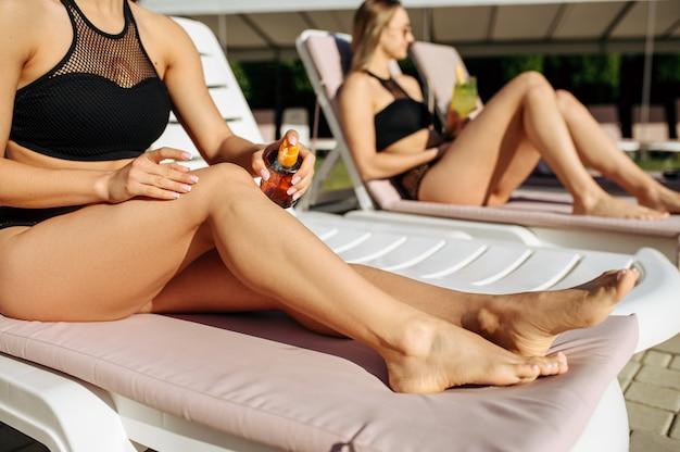 Seksowna kobieta stosuje spray do opalania na solarium, opalanie. piękne dziewczyny relaksują się przy basenie w słoneczny dzień, letnie wakacje atrakcyjnych dziewczyn