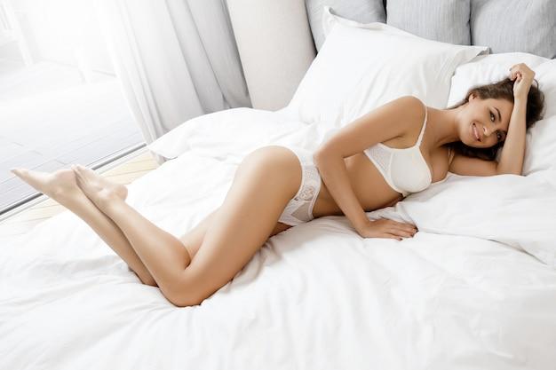 Seksowna kobieta w białej bieliźnie w łóżku
