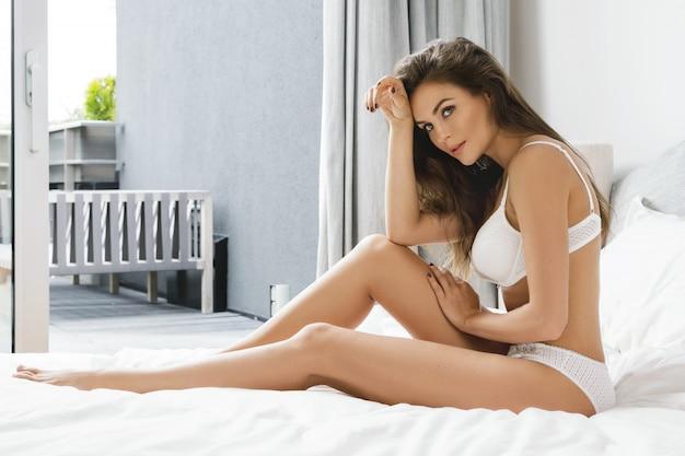 Seksowna kobieta w białej bielizny obsiadaniu na łóżku