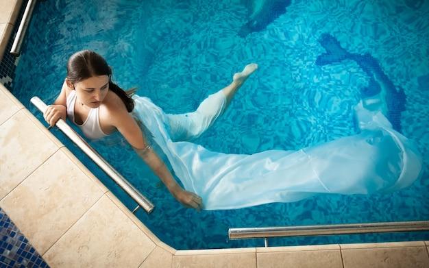 Seksowna kobieta w białej sukience pływająca obok krawędzi w basenie