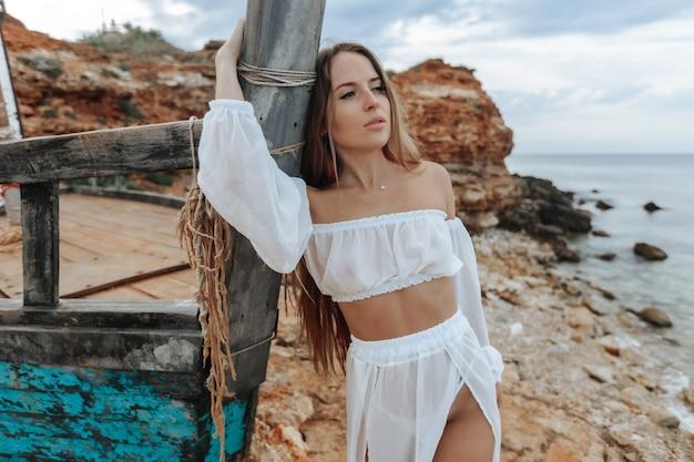 Seksowna kobieta w białej sukni na wraku statku na skalistym wybrzeżu