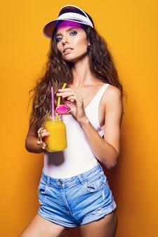 Seksowna kobieta w białym stroju kąpielowym i niebieskich jeansowych spodenkach, modny daszek trzyma szklankę świeżego drinka stojąc na żółtym, pomarańczowym gorącym tle