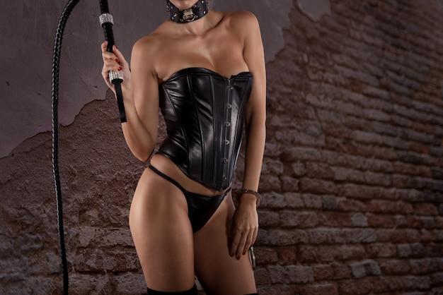 Seksowna kobieta w bieliźnie w stylu bdsm z biczem w ręku