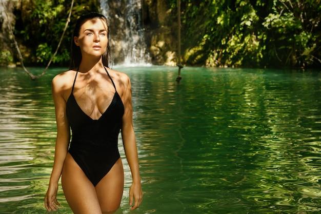 Seksowna kobieta w ciemnozielonej dżungli z siklawą na tle