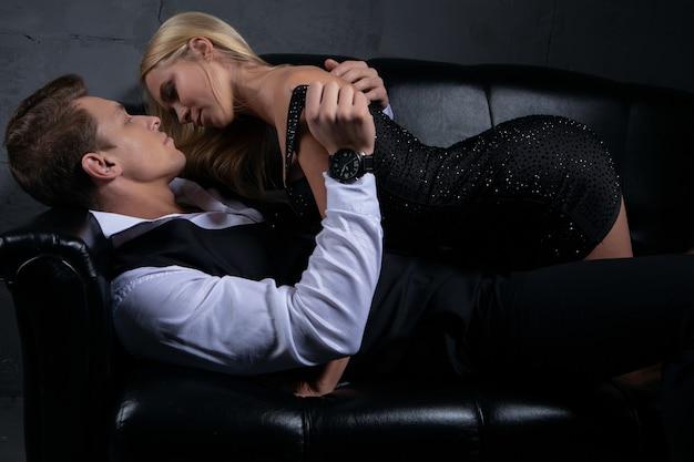 Seksowna kobieta w czarnej sukni całuje pięknego mężczyznę leżącego na kanapie.