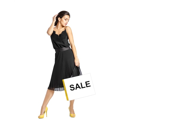 Seksowna kobieta w czarnej sukni z torby na zakupy na białym tle.