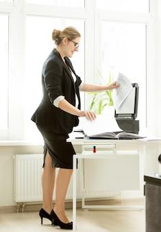 Seksowna kobieta w czarnym garniturze robiąca kopie dokumentów na ksero