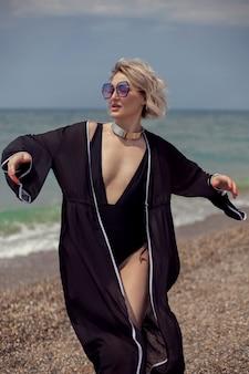 Seksowna kobieta w czarnym stroju kąpielowym i okularach przeciwsłonecznych stoi latem na plaży