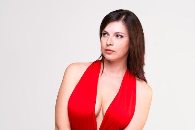 Seksowna kobieta w czerwonej sukience z głębokim dekoltem na szarej ścianie