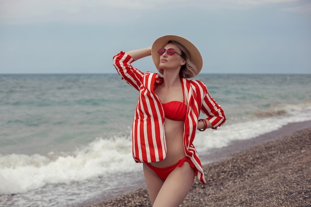 Seksowna kobieta w czerwonym kostiumie kąpielowym, pasiastej marynarce, okularach przeciwsłonecznych i słomkowym kapeluszu stoi latem na plaży nad morzem