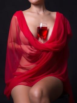 Seksowna kobieta w czerwonym obrusem i kieliszkami winorośli