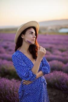 Seksowna kobieta w niebieskiej sukience i słomkowym kapeluszu na kwitnących lawendowych polach o zachodzie słońca cieszy się naturą