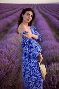 Seksowna kobieta w niebieskiej sukience i słomkowym kapeluszu patrzy w kamerę na kwitnących lawendowych polach o zachodzie słońca cieszy się naturą