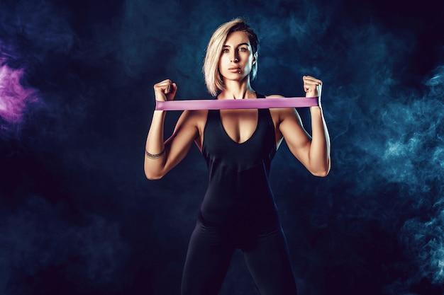 Seksowna kobieta w odzieży sportowej przy użyciu zespołu oporu w jej rutyny ćwiczeń. młoda kobieta wykonuje ćwiczenia fitness na czarnej ścianie z dymem. izolować