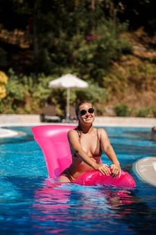Seksowna kobieta w okularach przeciwsłonecznych z uśmiechem na twarzy w stroju kąpielowym leży na różowym materacu w basenie. zrelaksuj się przy basenie w upalny, słoneczny dzień. koncepcja wakacji