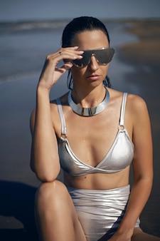 Seksowna kobieta w srebrnym kostiumie kąpielowym i okularach przeciwsłonecznych siedzi latem na plaży