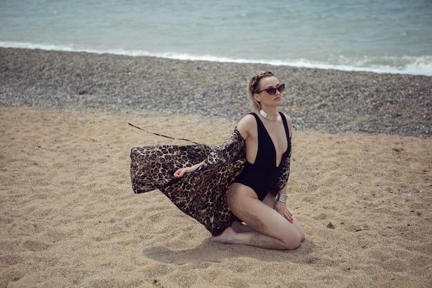 Seksowna kobieta w srebrnym kostiumie kąpielowym i okularach przeciwsłonecznych siedzi na plaży